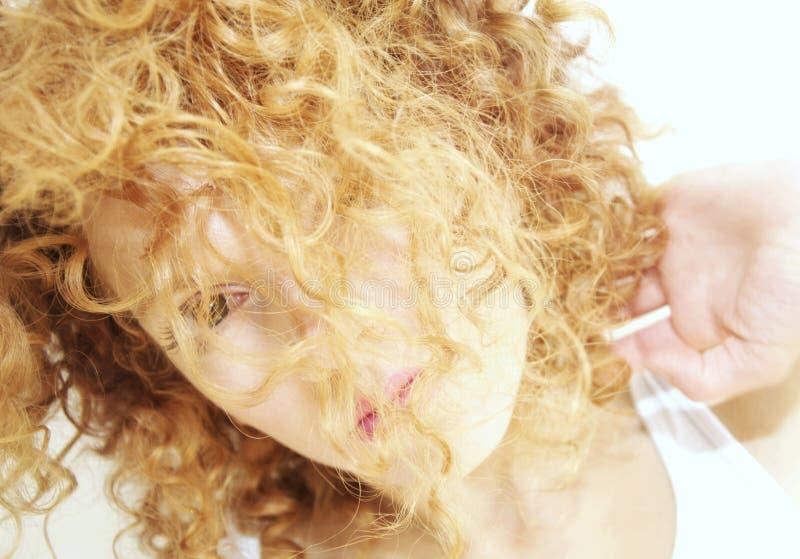 Jeune femme avec le visage caché par le cheveu bouclé photo stock