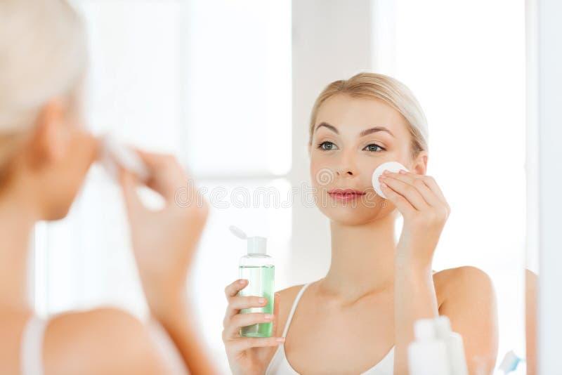 Jeune femme avec le visage de lavage de lotion à la salle de bains images libres de droits