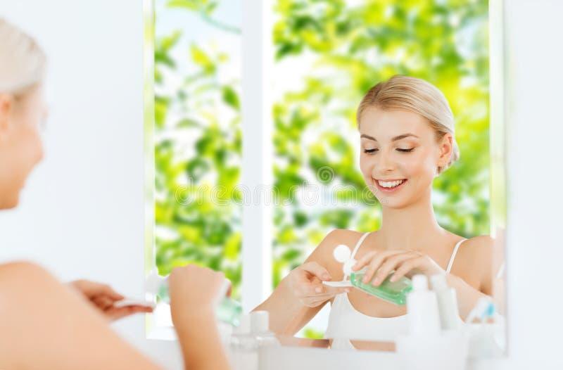 Jeune femme avec le visage de lavage de lotion à la salle de bains image libre de droits