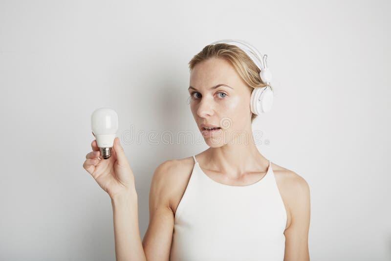 Jeune femme avec les écouteurs blancs et la lumière électrique avec le fond vide photos stock