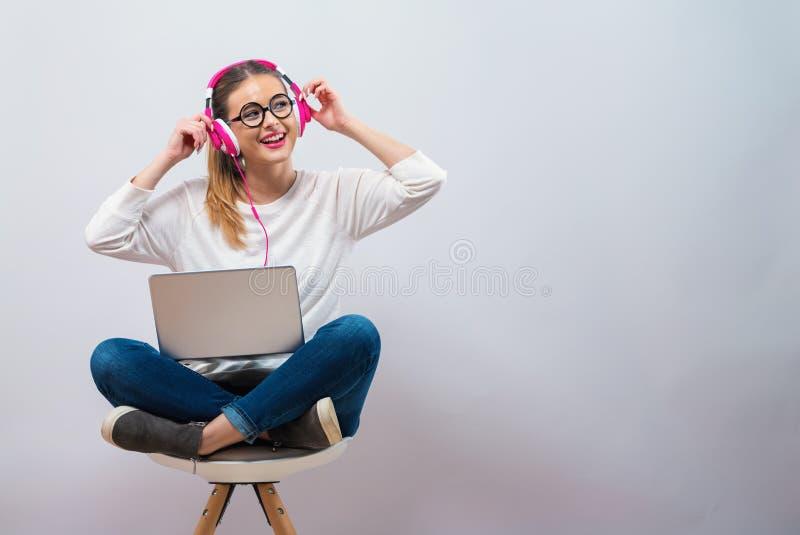 Jeune femme avec les écouteurs et son ordinateur portable photos stock