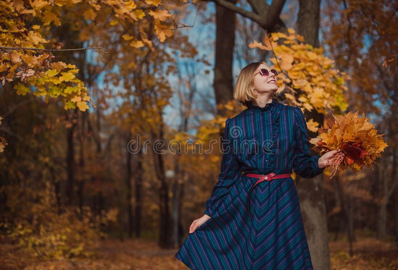 Jeune femme avec les cheveux blonds portant la robe bleue marchant en parc d'automne photographie stock