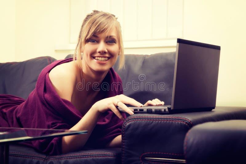 Jeune femme avec les cheveux blonds travaillant sur son ordinateur portable à la maison image libre de droits