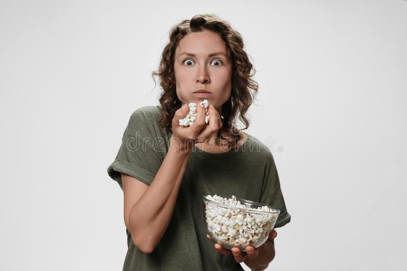 Jeune femme avec les cheveux boucl?s mangeant du ma?s ?clat?, observant un film ou des ?missions de TV photographie stock libre de droits