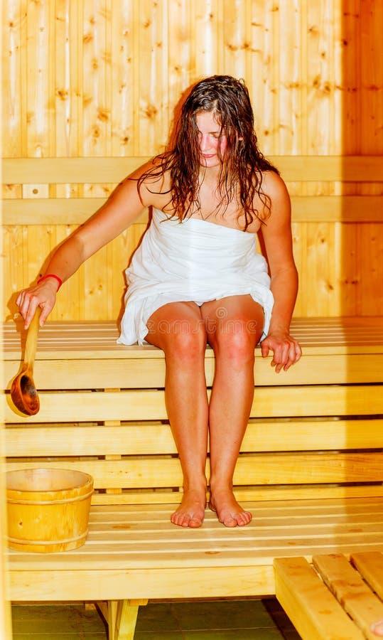 Jeune femme avec les cheveux bruns appréciant le bien-être de sauna photo stock