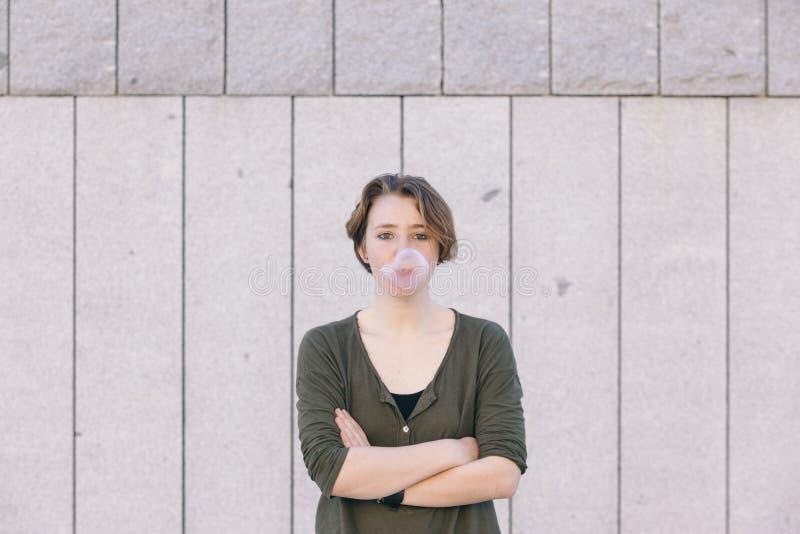 Jeune femme avec les cheveux courts soufflant un bubble-gum rose image stock