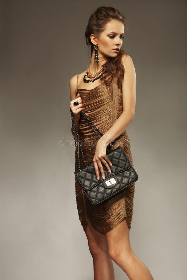 Jeune femme avec les cheveux, la robe d'or et les bijoux et le handb goupillés images stock