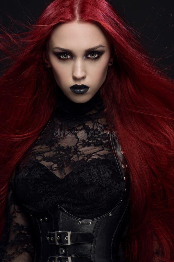 Jeune femme avec les cheveux rouges dans le costume gothique noir photographie stock libre de droits