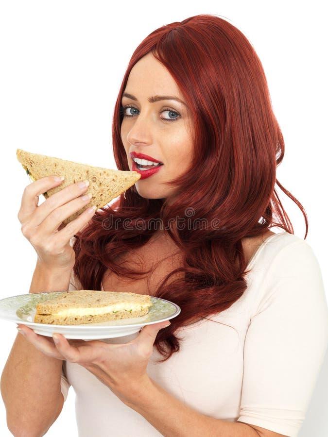 Jeune femme avec les cheveux rouges mangeant un sandwich à pain de Brown photos stock