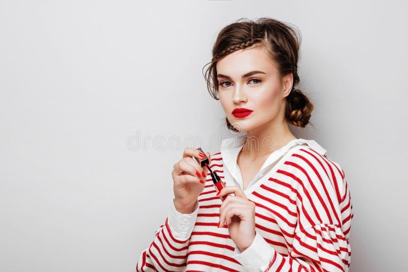 Jeune femme avec les l?vres rouges sur le joli visage ?motif dans la robe ?l?gante tenant le rouge ? l?vres de maquillage dans le photos libres de droits