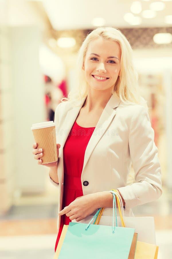Jeune femme avec les paniers et le café dans le mail photographie stock