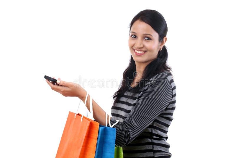 Jeune femme avec les sacs à provisions et le téléphone portable photo stock
