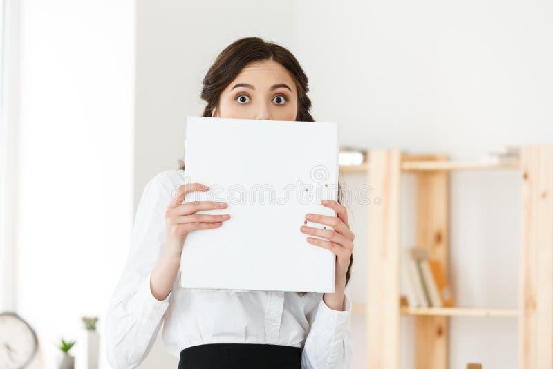 Jeune femme avec les yeux étonnés jetant un coup d'oeil par derrière l'affiche de papier Femme d'affaires tenant la grande banniè photographie stock
