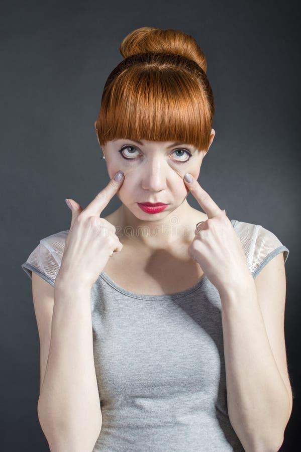 Jeune femme avec les yeux fatigués sur le fond noir Massage facial négatif photographie stock