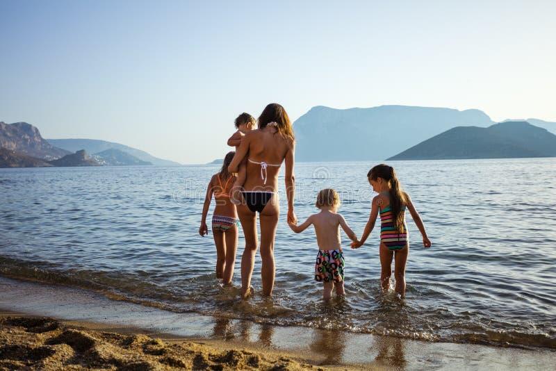 Jeune femme avec quatre enfants marchant en eaux de mer photos libres de droits