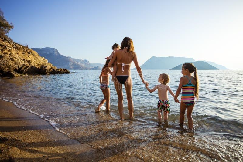 Jeune femme avec quatre enfants marchant en eaux de mer images libres de droits