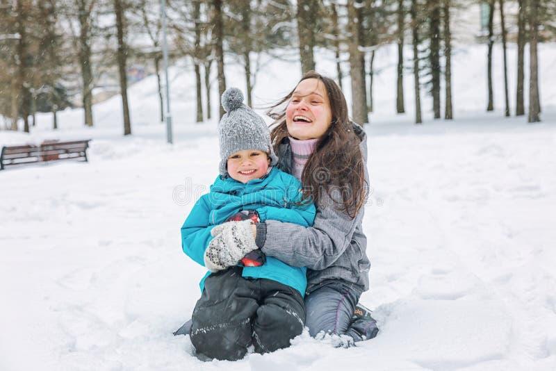 Jeune femme avec son petit fils jouant dans la neige en hiver photo stock