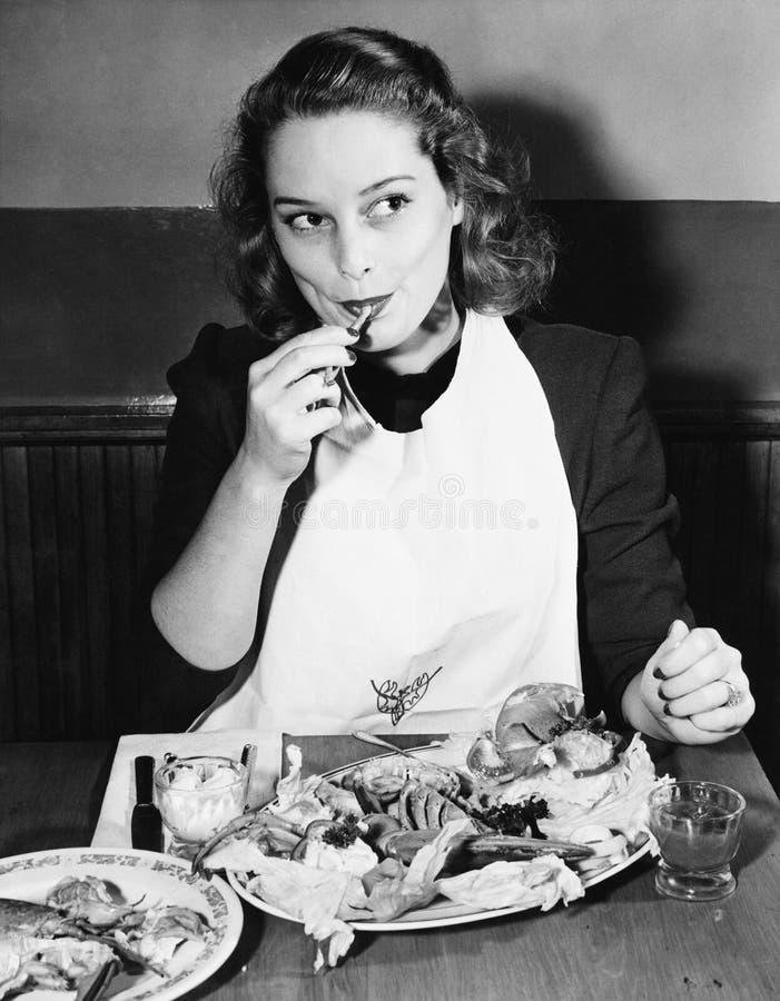 Jeune femme avec un bavoir mangeant le homard (toutes les personnes représentées ne sont pas plus long vivantes et aucun domaine  photographie stock libre de droits
