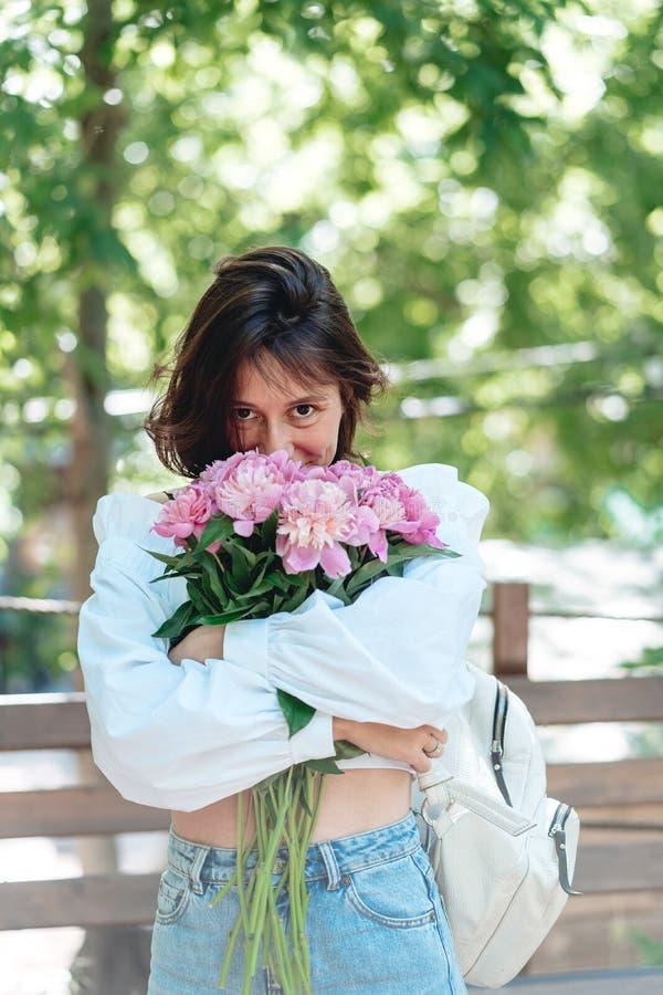 Jeune femme avec un bouquet des pivoines roses photo stock