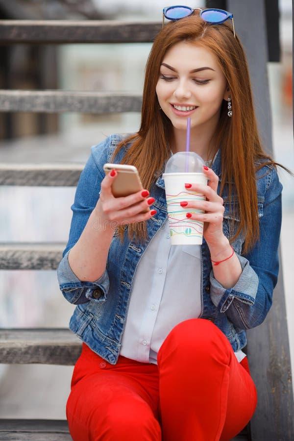 Jeune femme avec un cocktail, lisant un message textuel sur la rue photos libres de droits