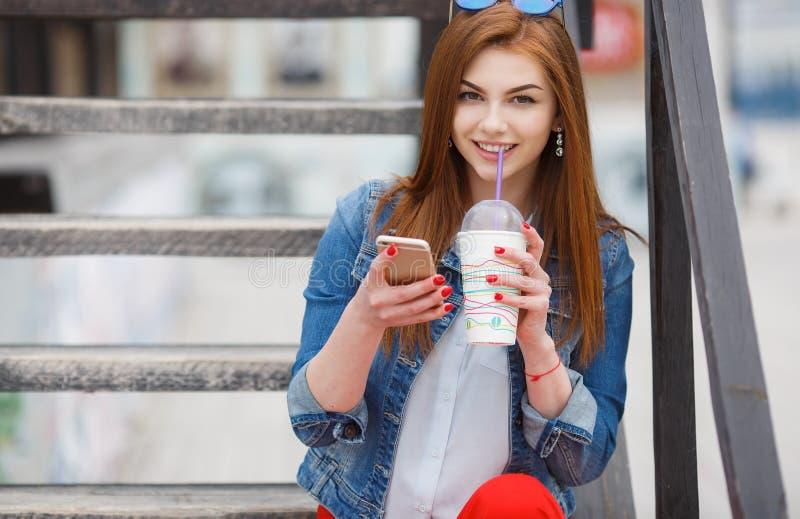 Jeune femme avec un cocktail, lisant un message textuel sur la rue photographie stock libre de droits