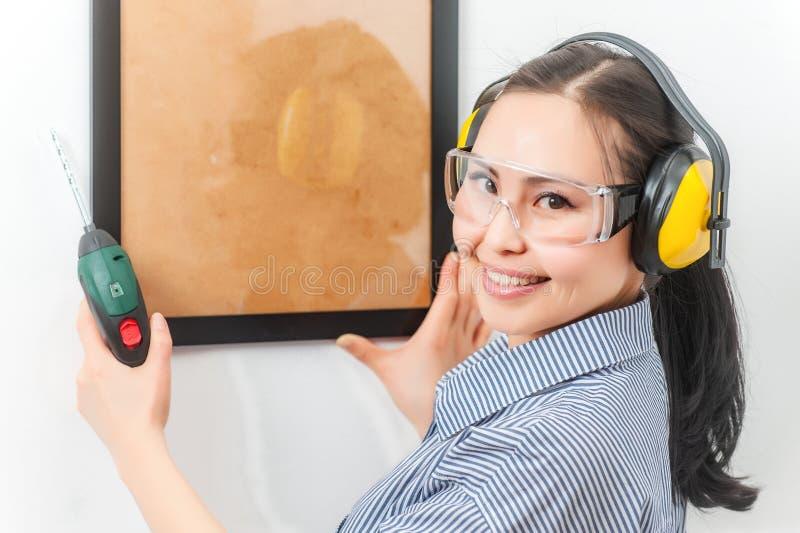 Jeune femme avec un foret image stock