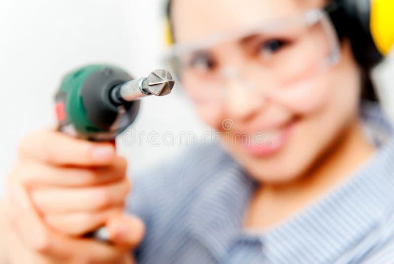 Jeune femme avec un foret photographie stock libre de droits