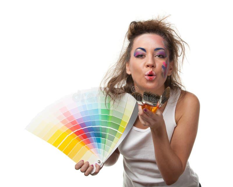 Jeune femme avec un guide et des pinceaux de couleur. image libre de droits