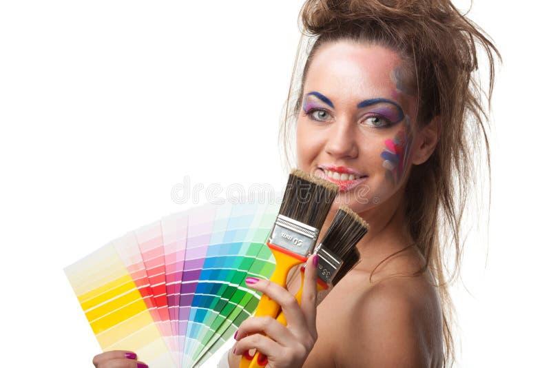 Jeune femme avec un guide et des pinceaux de couleur. photo stock