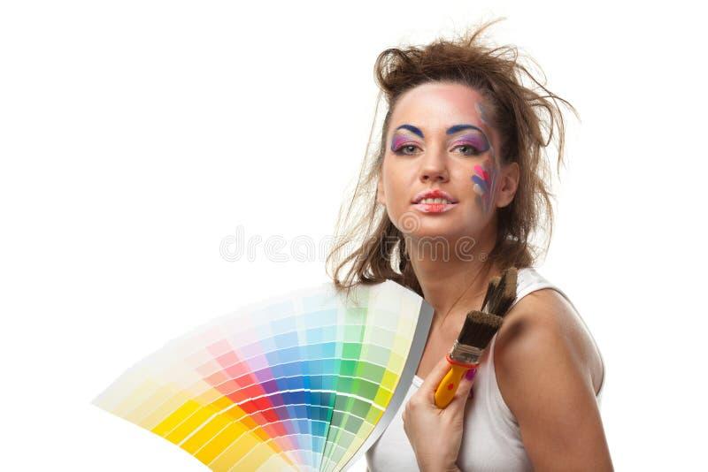 Jeune femme avec un guide et des pinceaux de couleur. image stock