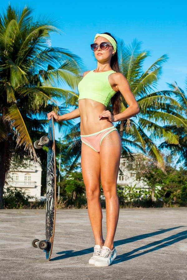 Jeune femme avec un longboard Adolescente occasionnelle à la mode de hippie avec une planche à roulettes photo libre de droits