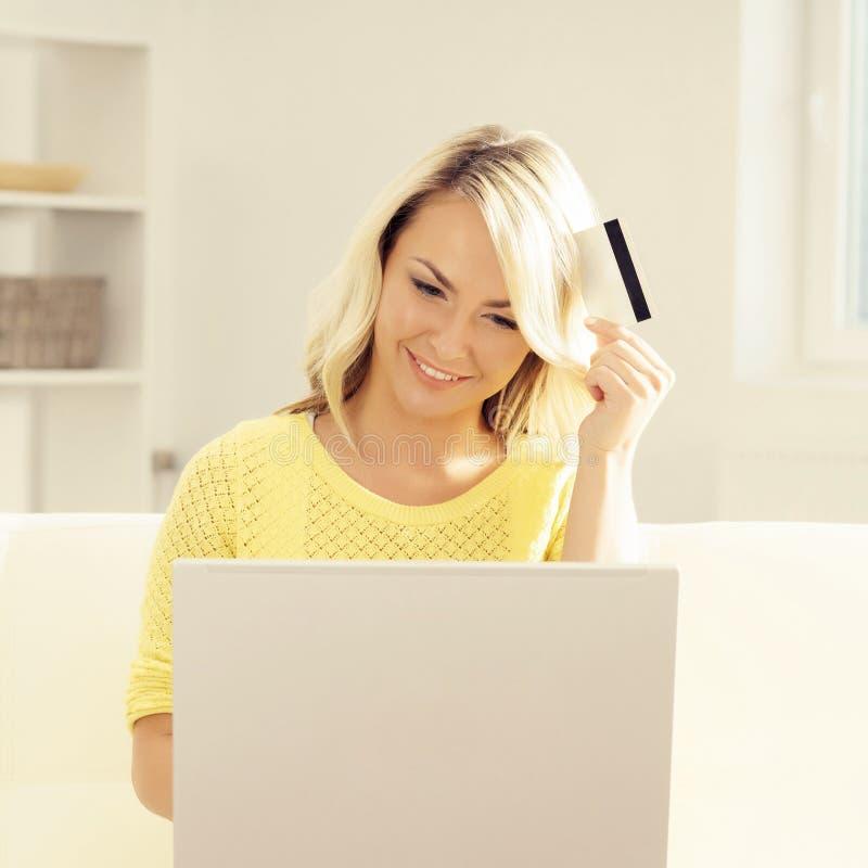 Jeune femme avec un ordinateur portable tenant une carte de crédit photos libres de droits