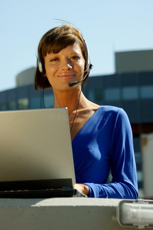 Jeune femme avec un ordinateur portatif et un écouteur photos stock