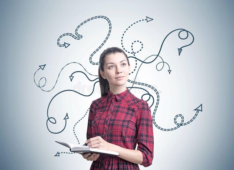 Jeune femme avec un planificateur, flèches image stock