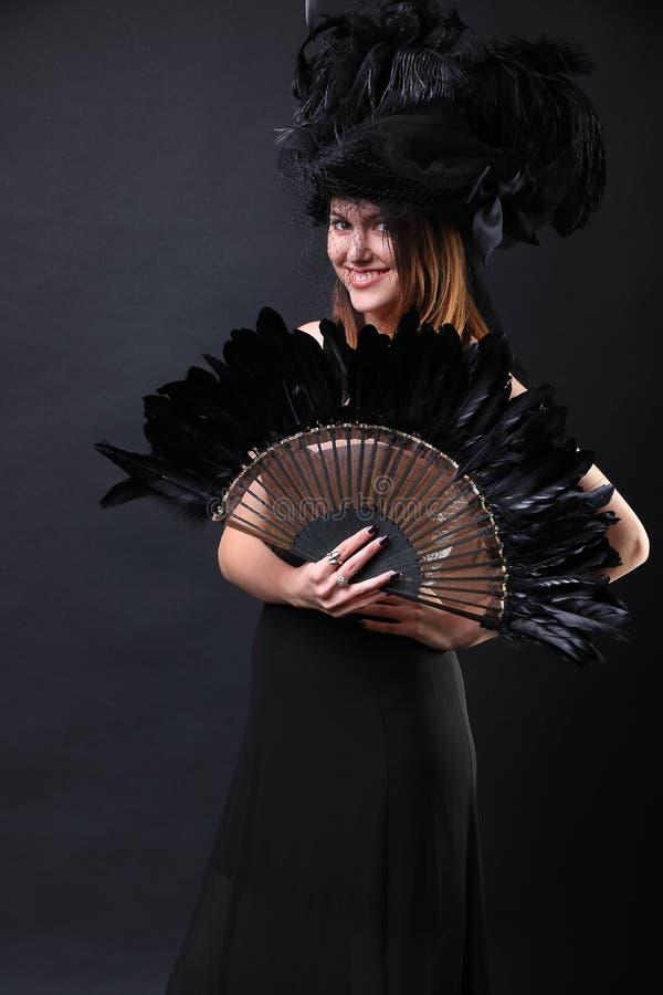 Jeune femme avec un sourire noir de fan et de chapeau de plume image stock