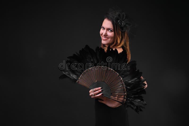 Jeune femme avec un sourire noir de fan de plume image libre de droits