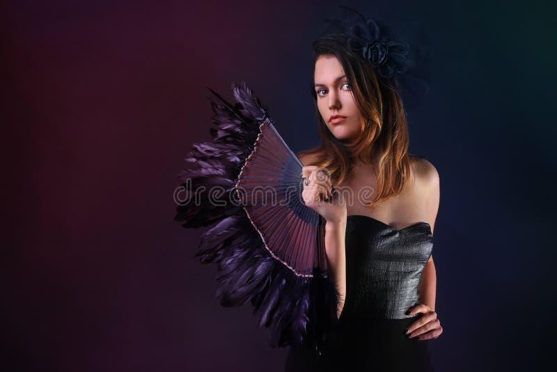 Jeune femme avec une fan et un chapeau noirs de plume photos stock