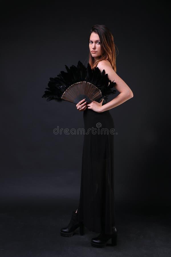 Jeune femme avec une fan noire de plume image stock