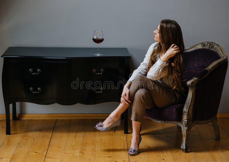 Jeune femme avec une glace de vin photographie stock