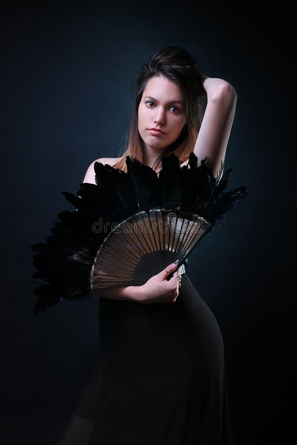 Jeune femme avec une pose noire de fan de plume photos libres de droits