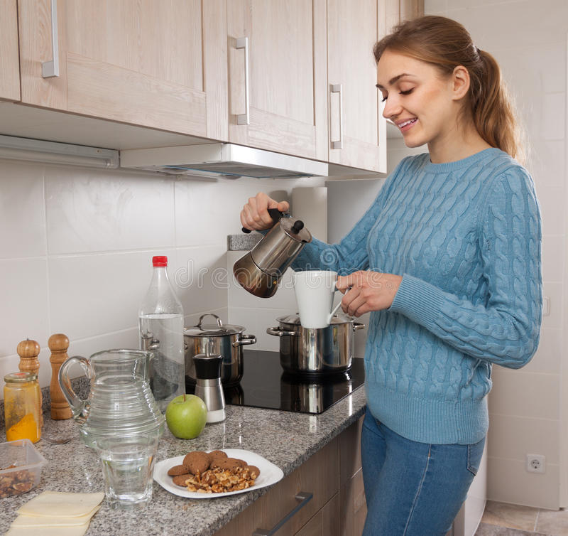 Jeune femme avec une tasse de café dans la cuisine à la maison image libre de droits