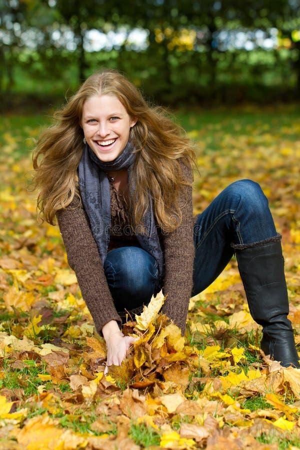 Jeune femme ayant l'amusement en automne image stock