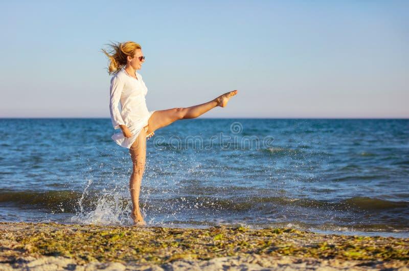 Jeune femme ayant l'amusement sur la plage photo stock