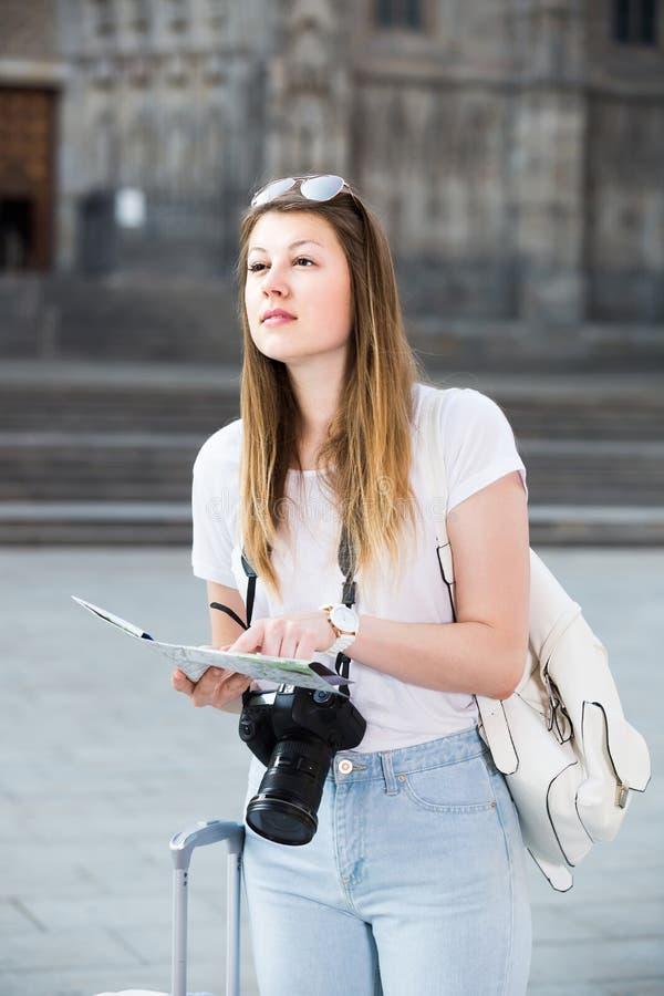 Jeune femme ayant la carte et recherchant son itinéraire dans la ville photos stock