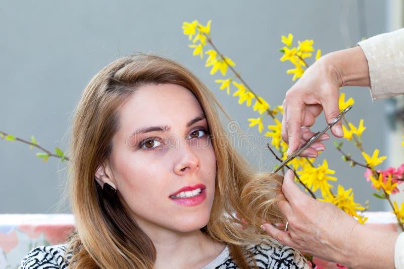Jeune femme ayant la coupe de cheveux photos stock
