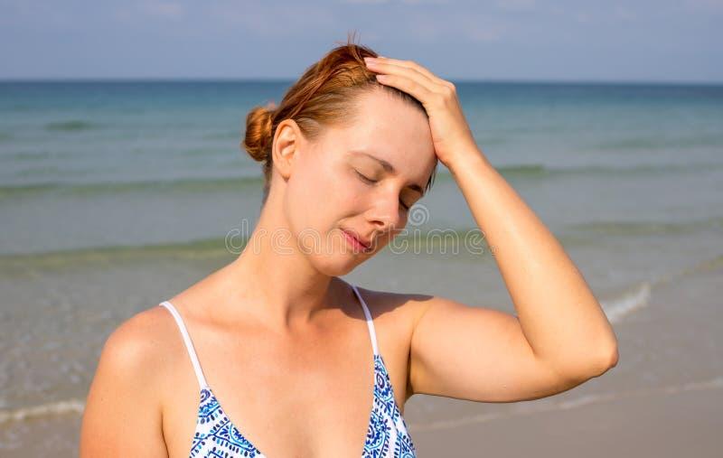 Jeune femme ayant la course de soleil Probl?me de sant? des vacances M?decine des vacances Le soleil dangereux image stock