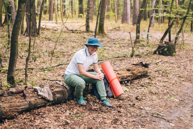 Jeune femme ayant la douleur de genou de sentiment de problème pendant le voyage dans la blessure de forêt sur le chemin de campe photo libre de droits