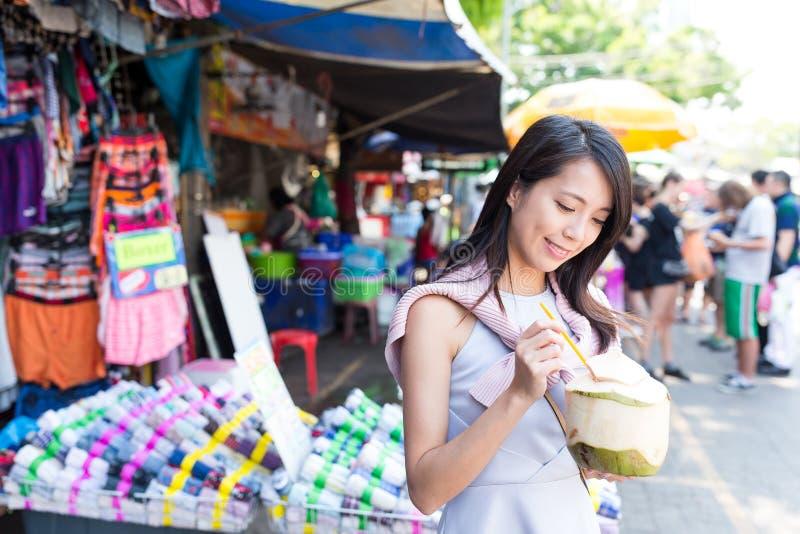 Jeune femme ayant la noix de coco juteuse sur le marché en plein air photographie stock libre de droits