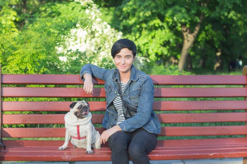 Jeune femme ayant le bon temps avec le roquet sur l'herbe verte, la jolie fille avec le jeu de chien dans le parc pendant le couc images libres de droits