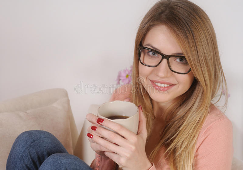 Jeune femme ayant le café à la maison images stock